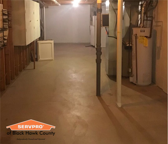 Empty basement with water heater and high ceiling.
