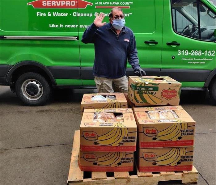 A jolly man waving and standing in front of a pallet of boxed food.