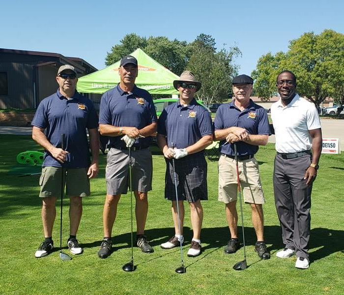 A group photo of 5 men with their golf tees in front of a bright green tent.