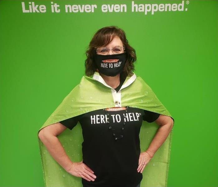 A woman wearing a black mask, a shirt that says here to help and a green cape.