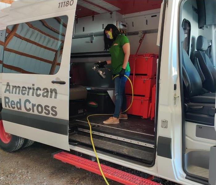 American Red Cross Transit with their side door open and a woman spraying a white mist in the truck.