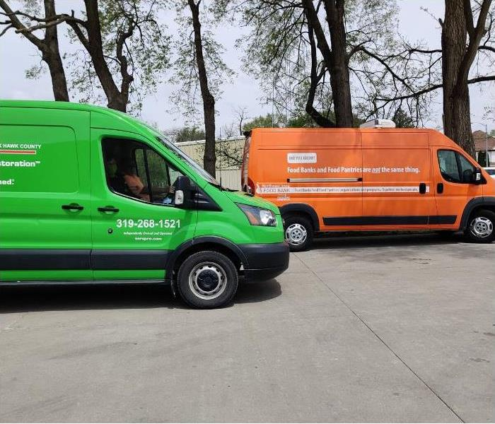 Green SERVPRO vehicle next to the Orange FOOD BANK vehicles.