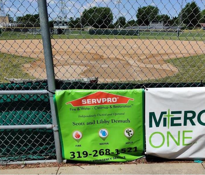 Diamond Baseball Field in front of a green fence with a bright green SERVPRO sign on it.