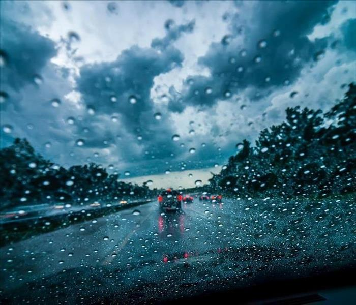 A car driver's perspective of being on the road with dark clouds looming over, and droplets on the windshield.