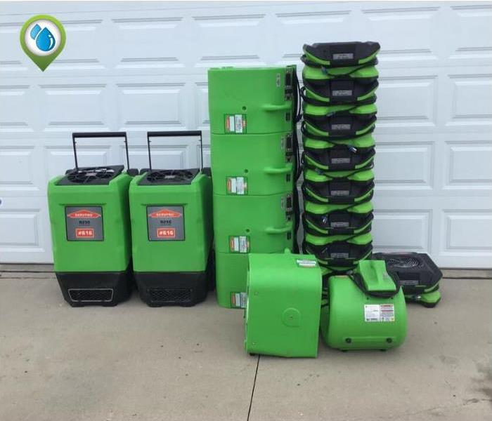 2 Green large dehumidifier, 4 stackable large Air movers, 9 small air movers that are stacked are in front of a white garage